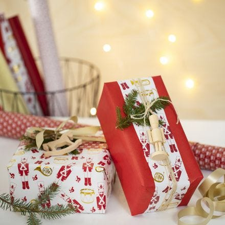 Creative Christmas Gift Wrapping with two kinds of Wrapping Paper and a wooden Figure