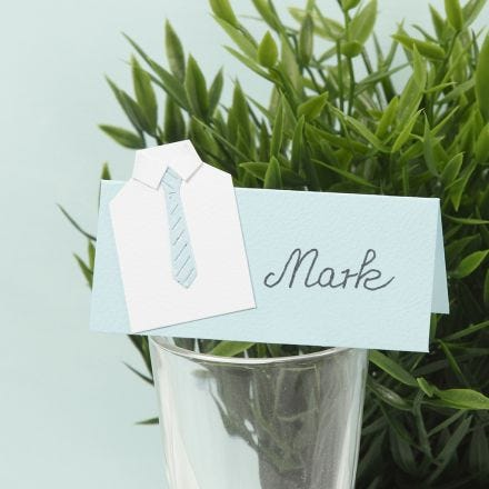 A place card for a confirmation party with a shirt from card and a paper tie