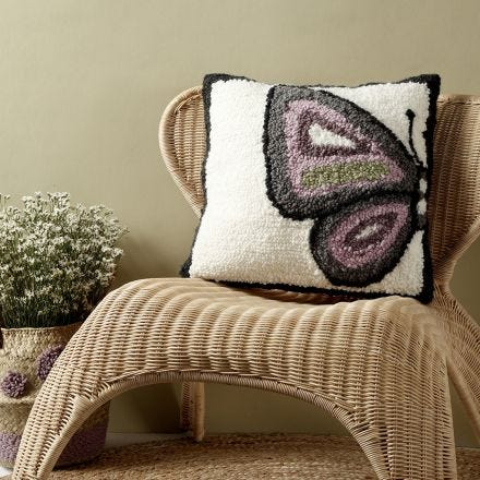 A cushion with a butterfly design made with a punch needle