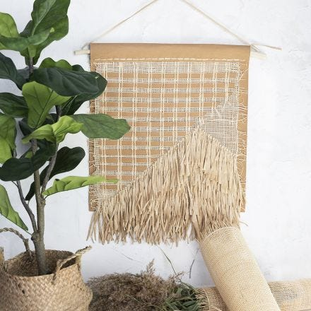 A wall hanging decoration from faux leather paper, rattan and raffia paper yarn