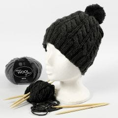 A hat knitted with a twist cable pattern and a pom-pom