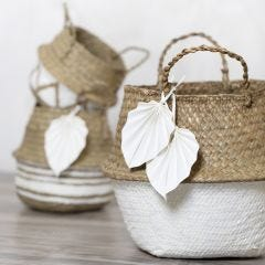 A sea grass basket decorated with craft paint and faux leather paper leaves