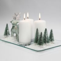 A Christmas Decoration with Candles, Reindeer, Trees and Snow on a Glass Dish