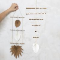 A mobile made from decorated bamboo sticks and faux leather paper