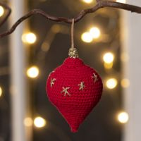 A teardrop-shaped Christmas hanging decoration crocheted from cotton yarn