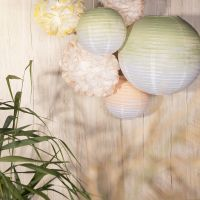 Party decorations from rice paper lamps and paper pom-poms painted with craft paint